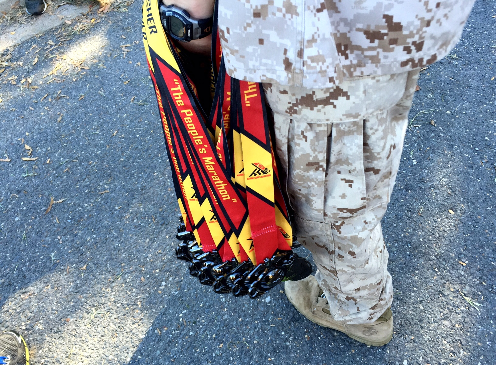 A Marine holding medals at the 2014 Marine Corps Marathon.