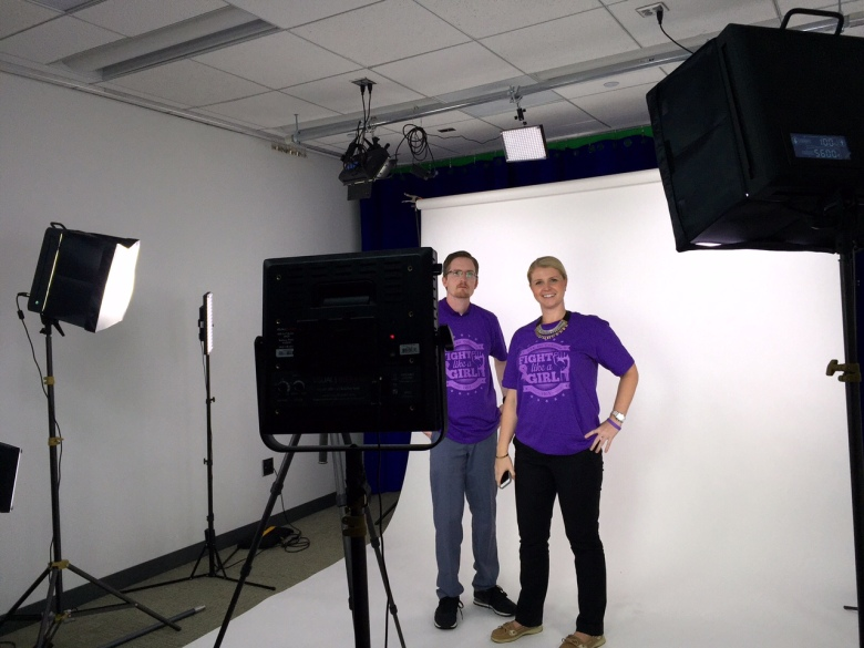 Colleagues Jeff and Erin posing in purple shirts.